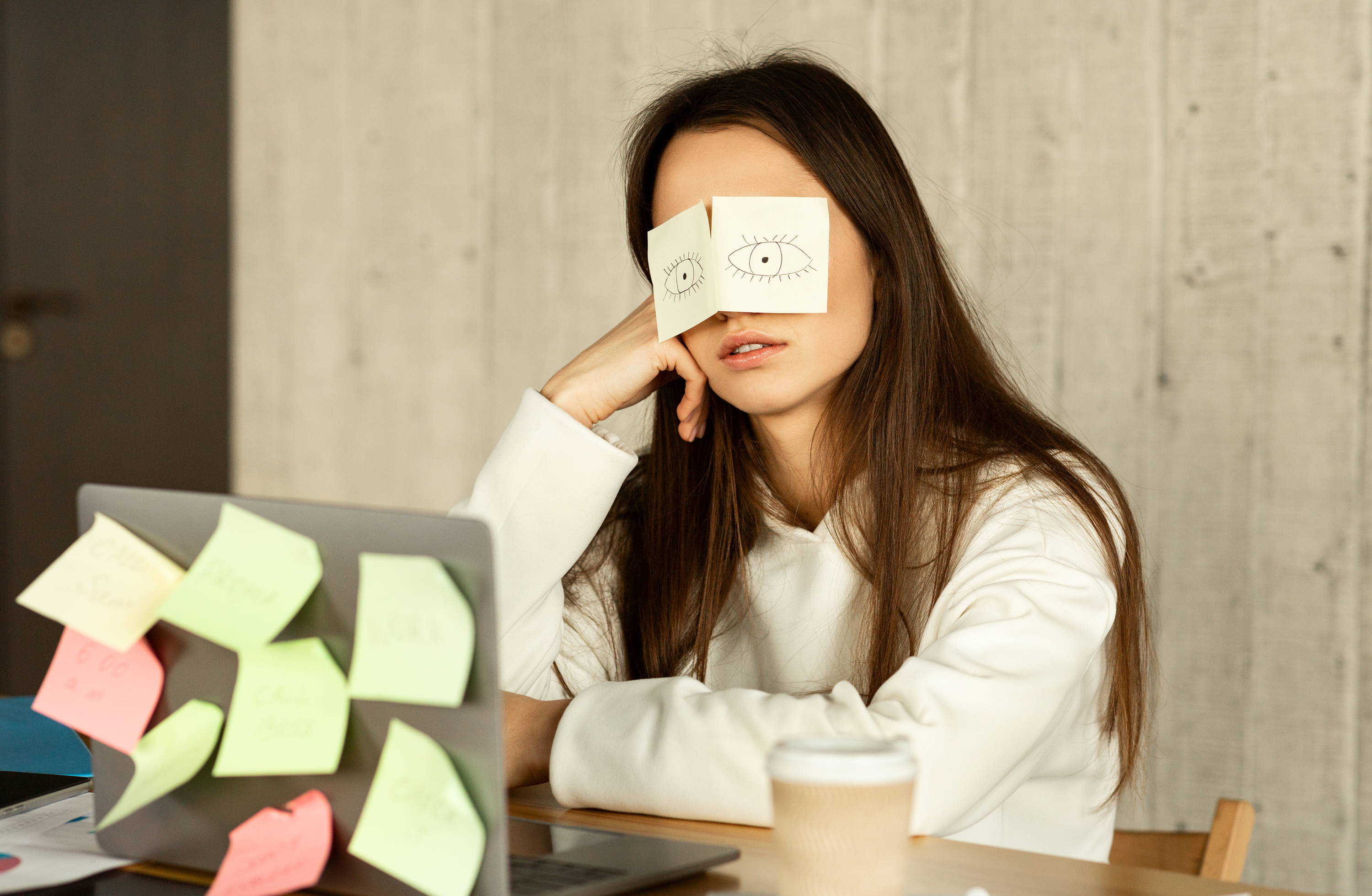 woman struggling with lack of focus, she has two post its with drawings of eyes over her own eyes