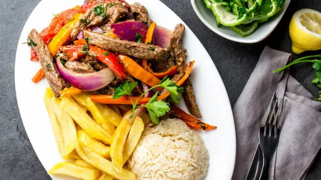lomo saltado - beef stir fry with peppers and onions with fries and rice