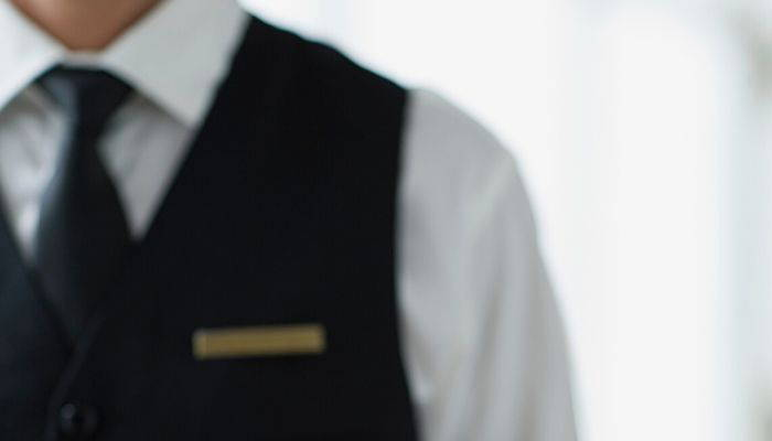Man wearing a black tie and vest uniform