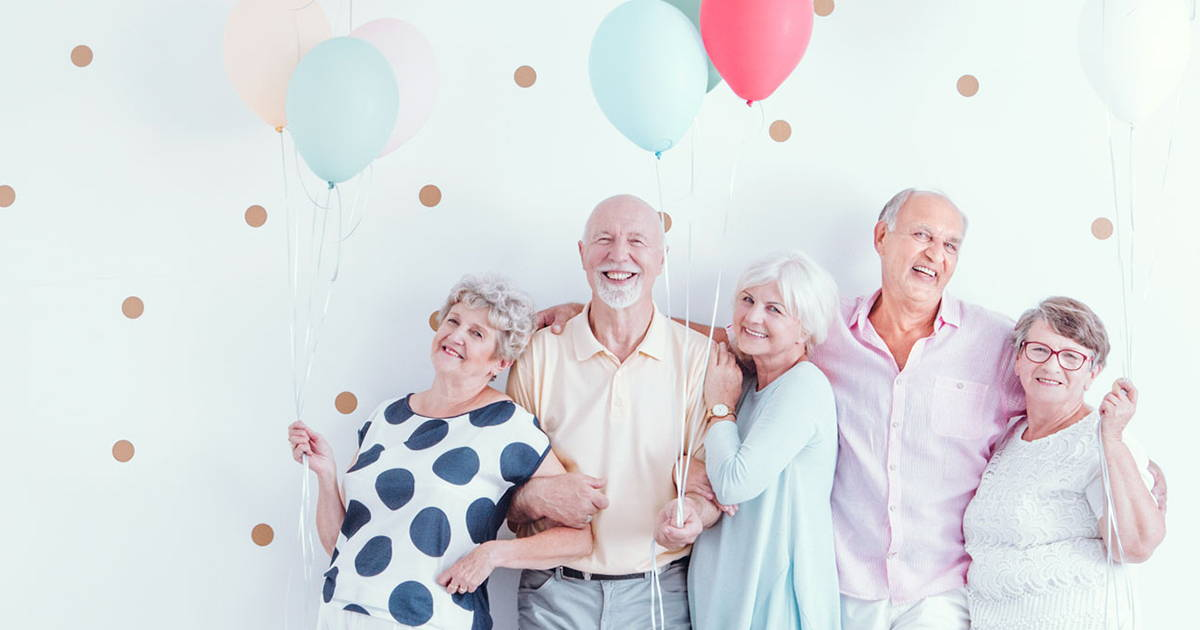 group of mature adults holding balloons smiling at the camera