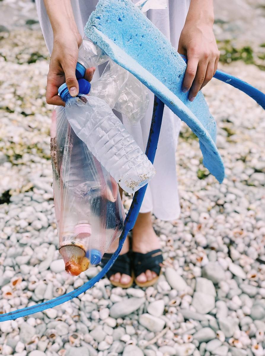 A lady on a beach with plastic waste she has collected