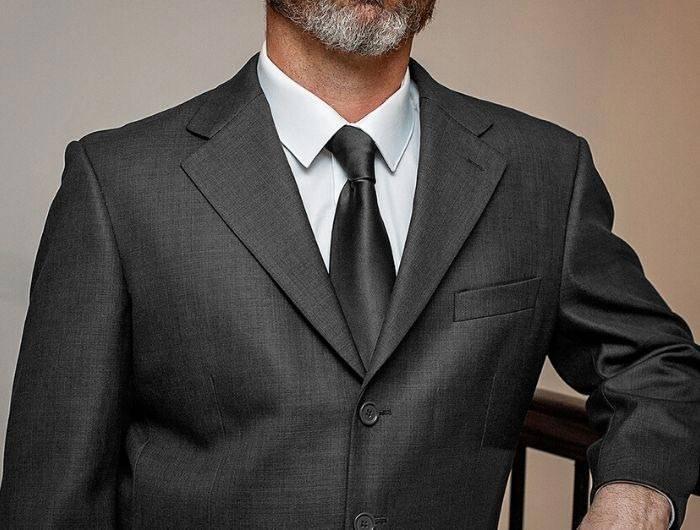 Man in dark gray suit with a black necktie