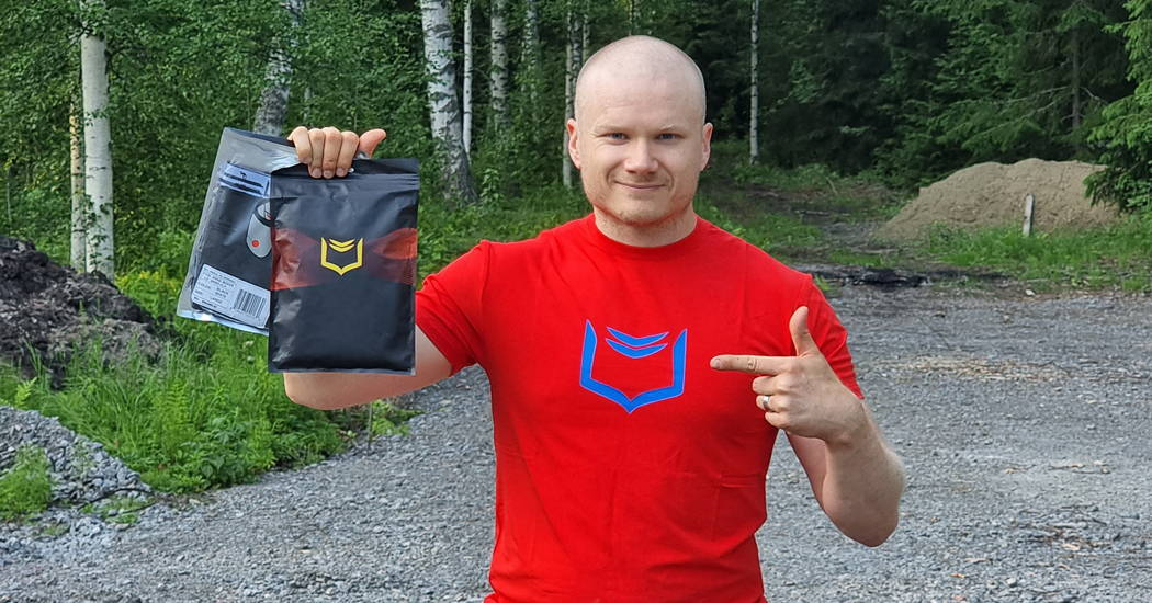 Beyond the Press host holding 2 pairs of sheath underwear and wearing red sheath bamboo shirt