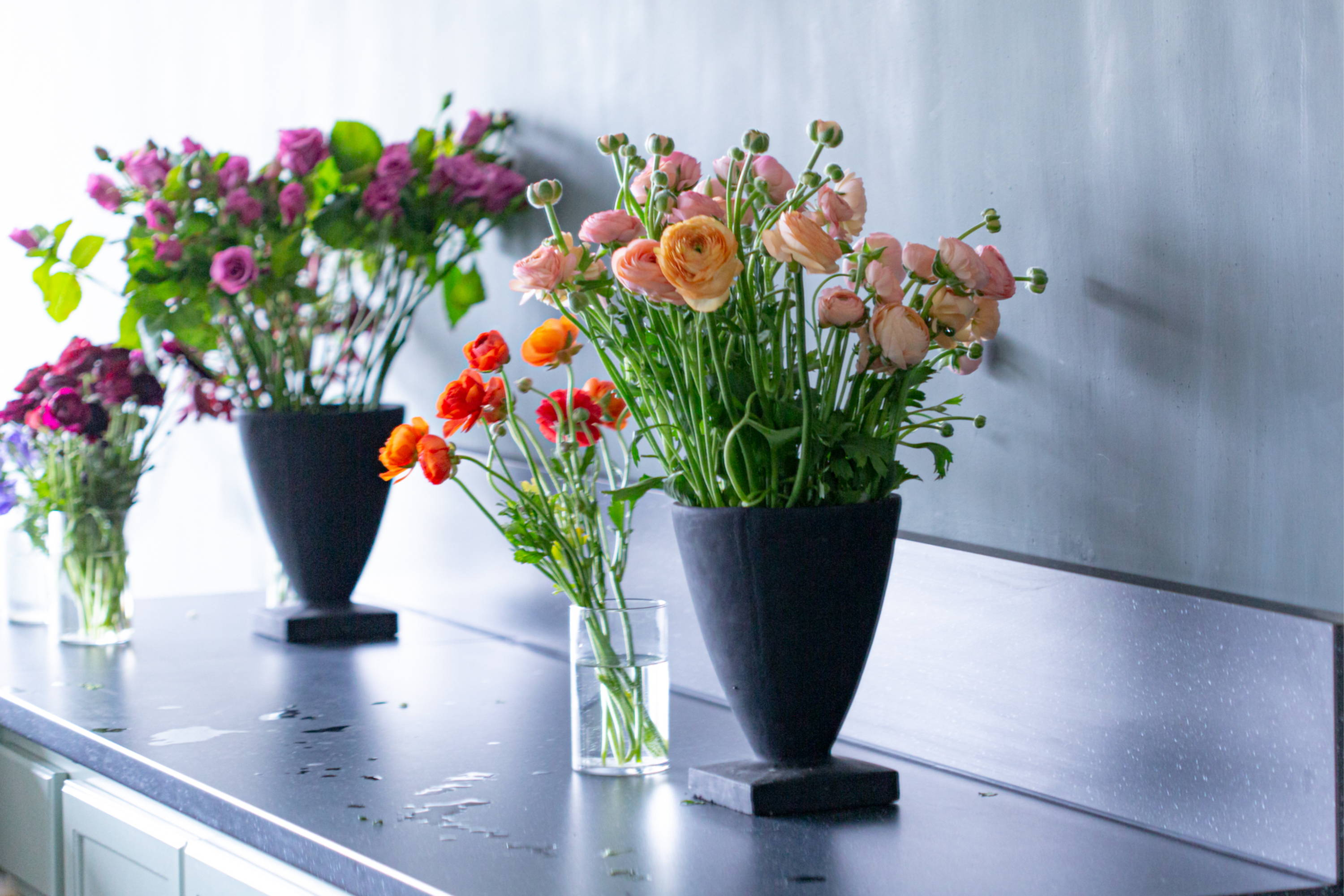 Image of floral arrangements in decorative vases on a dark countertop