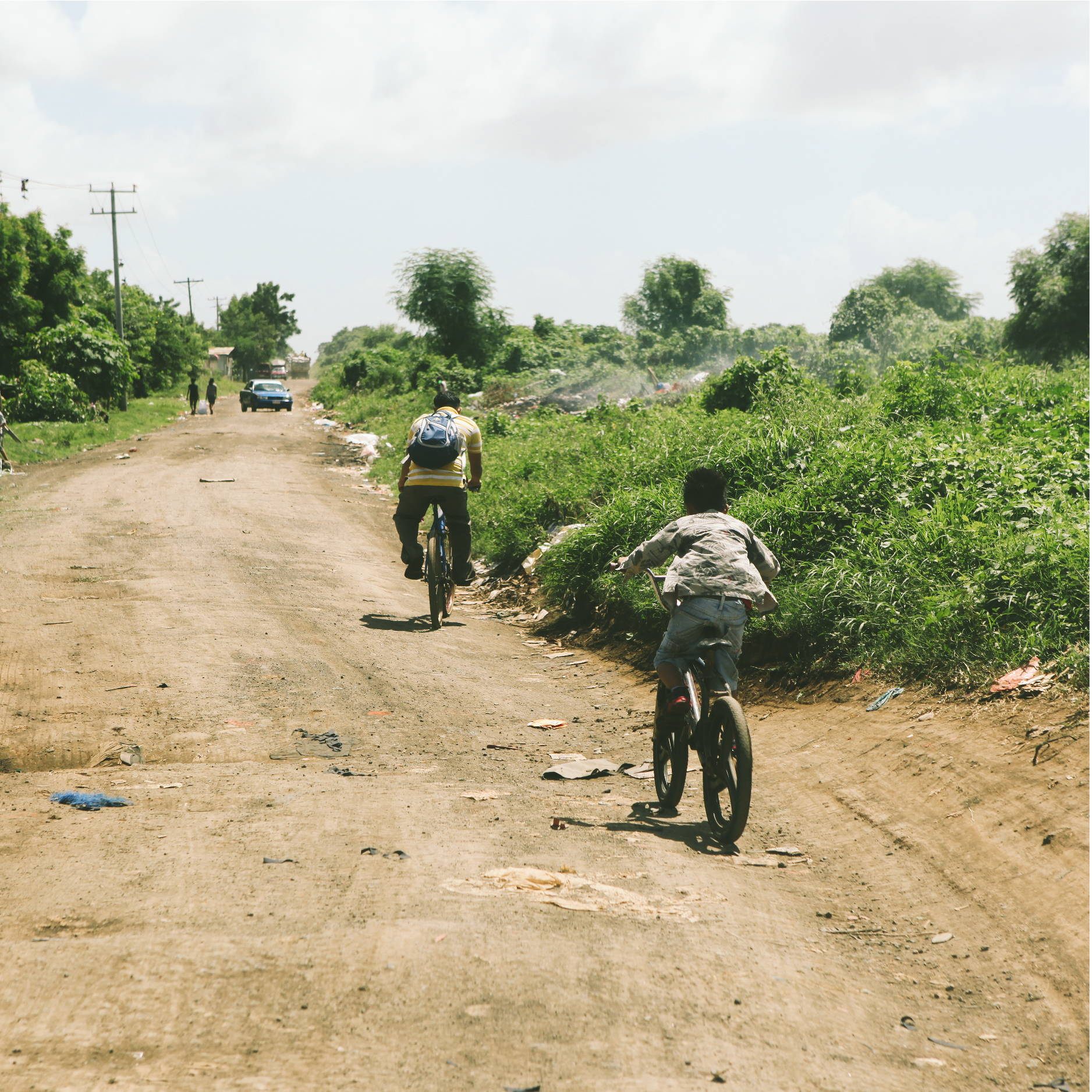 A man and his son ride their bikes down a trash lined dirt road in Nicaragua. The road is surrounded by overgrown vegetation.