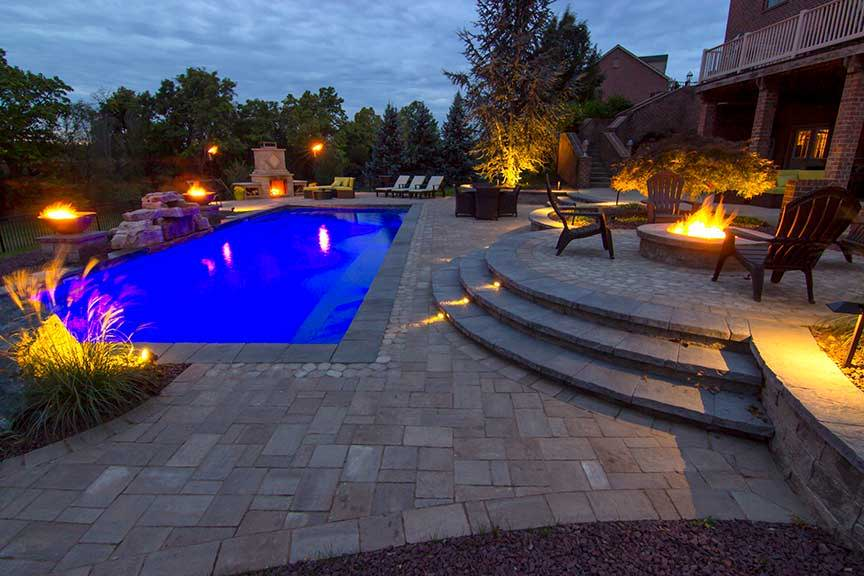 A stunning poolside patio surrounded by fire bowls and pits.