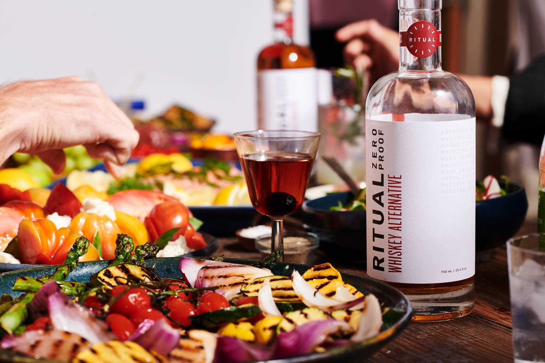 A dinner tables with vegetables, a non-alcoholic Manhattan mocktail, and a bottle of Ritual spirit-free whiskey.