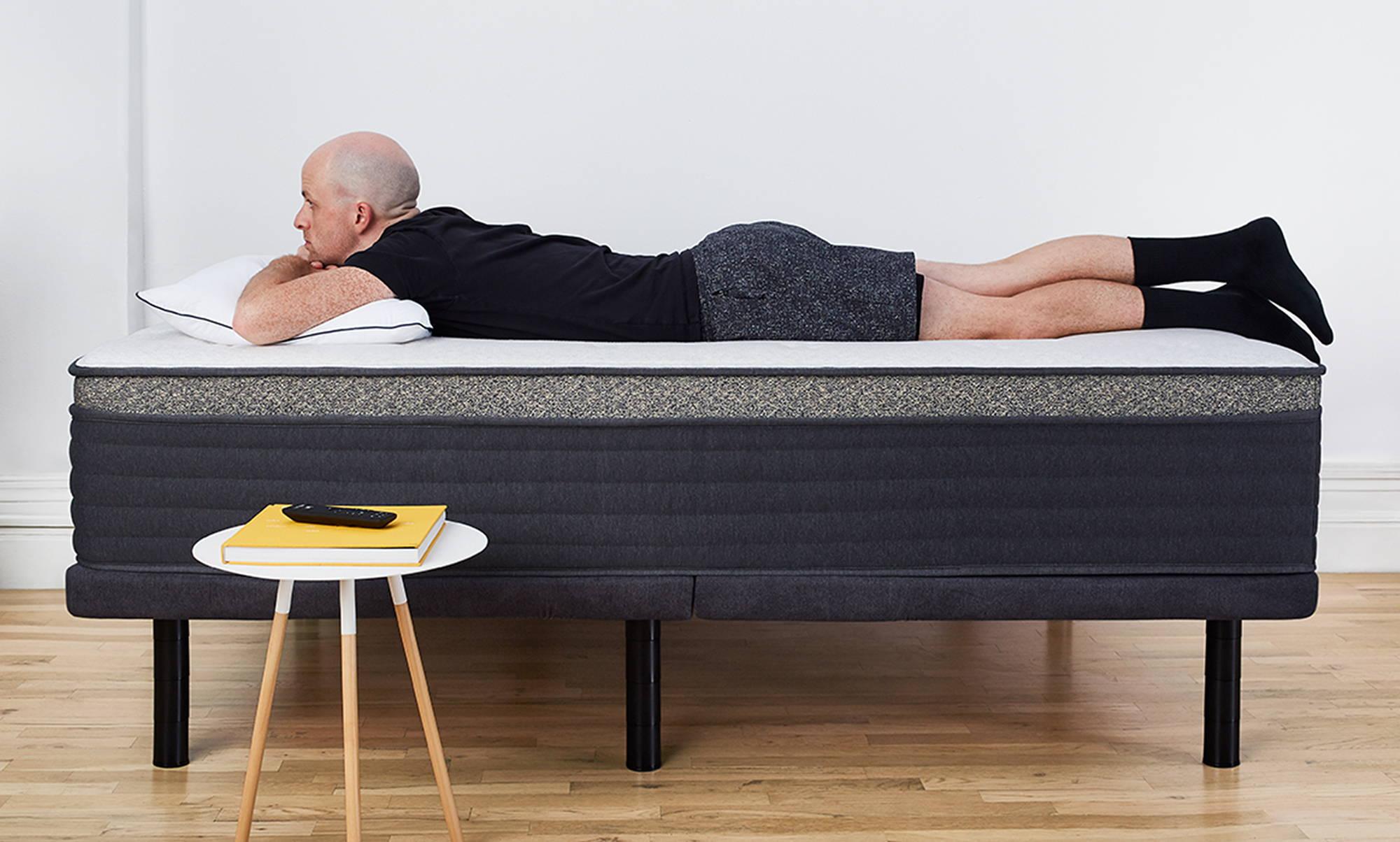 Man laying on Helix mattress on top of Helix Adjustable Base