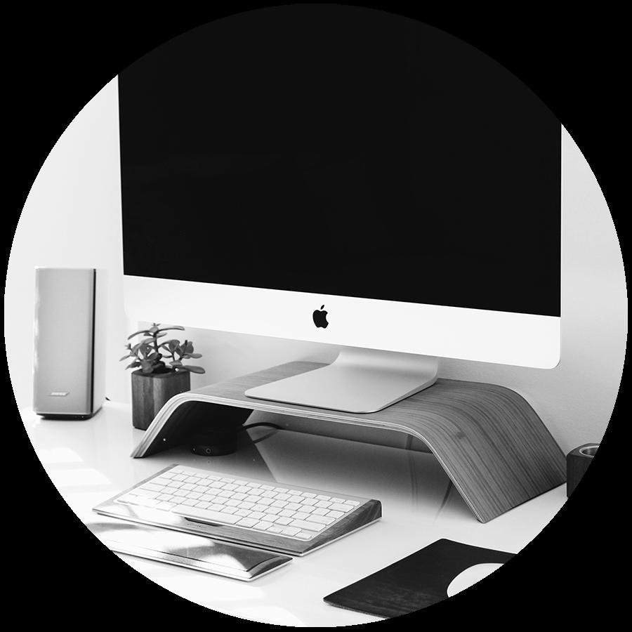 A Mac desktop monitor sitting on a wood stand