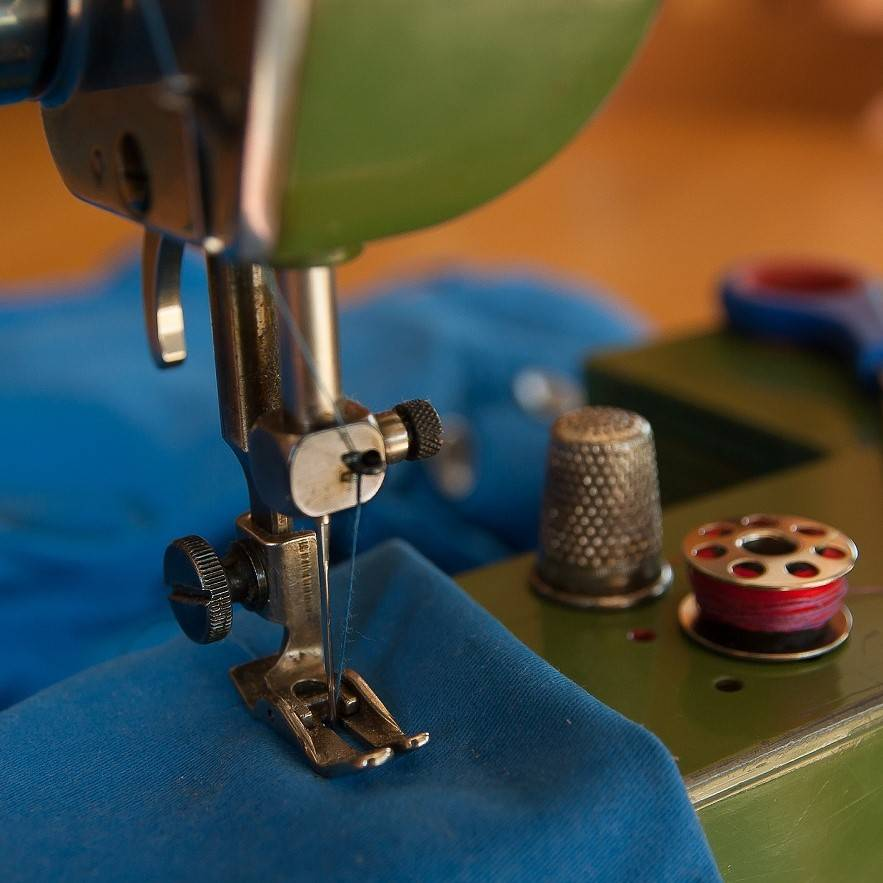 A close up photo of a green sewing machine working with blue fabric