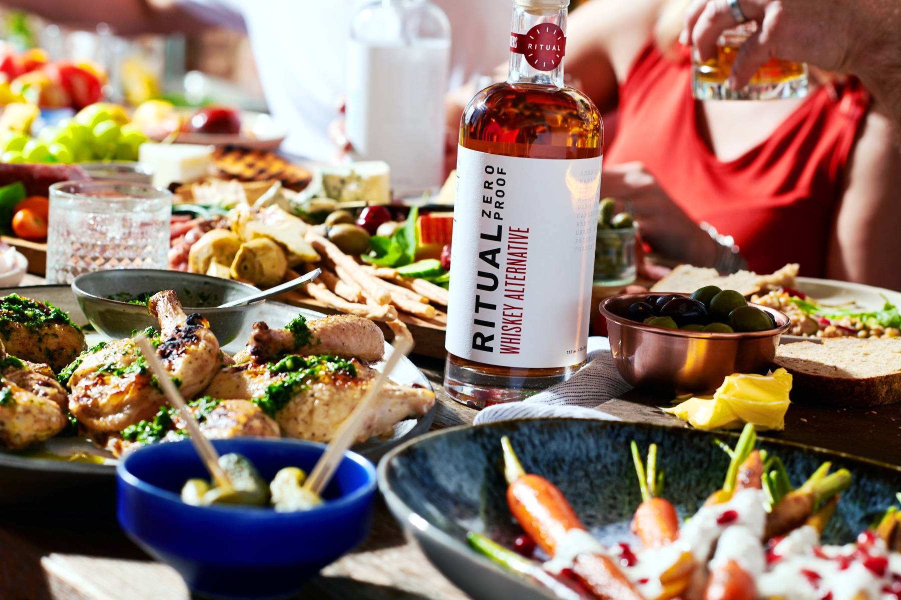 A bottle of Ritual non-alcoholic whiskey alternative on a dinner table along with chicken, olives and mocktails