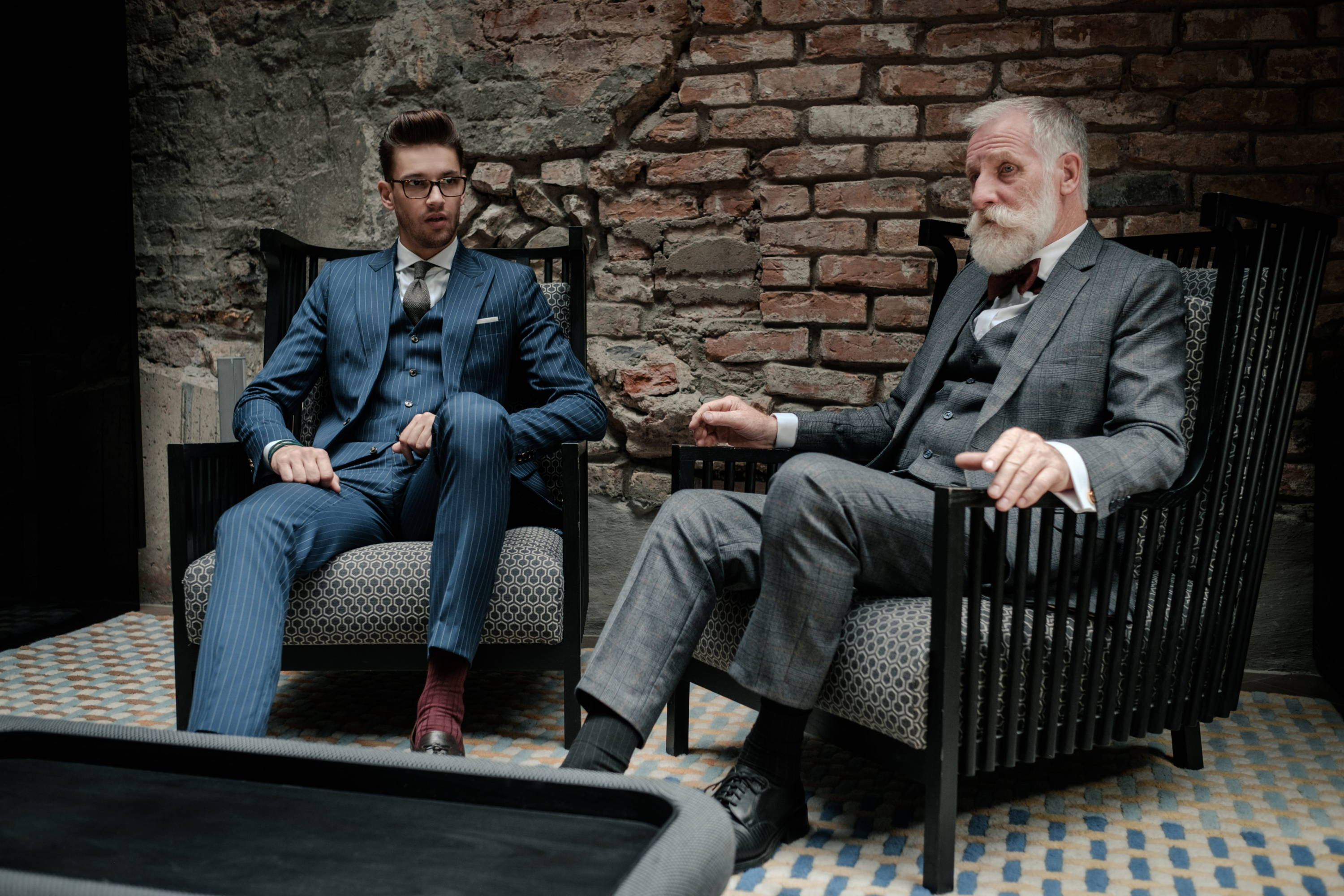 Two generations of well dressed men sit in classic check and pinstripe bespoke suits