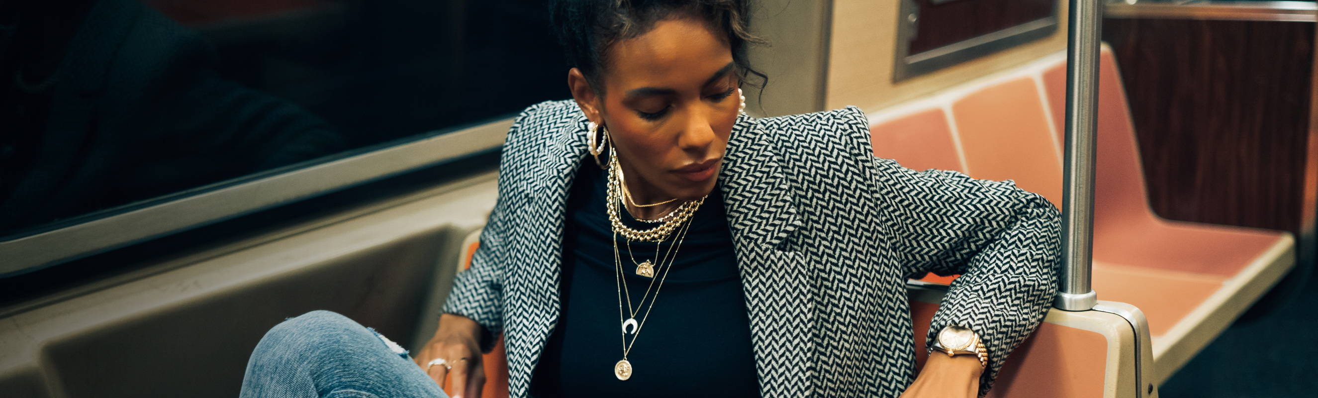 Model riding the subway wearing various Ring Concierge necklaces layered