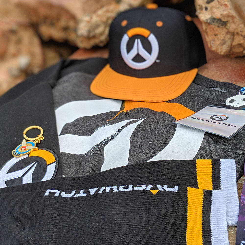 Photo showing a collection of Overwatch products, including a hat, socks, sweatshirt and more