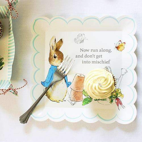 "Close up photo of one Peter Rabbit and Friends Large Plate from the Peter Rabbit Easter Party range. On this plate is a Beatrix Potter illustration of Peter Rabbit. He is on the left, beside some upturned flower pots and a watering can, two butterflies above him. Quotation from book ""Now run along and don't get into mischief."""