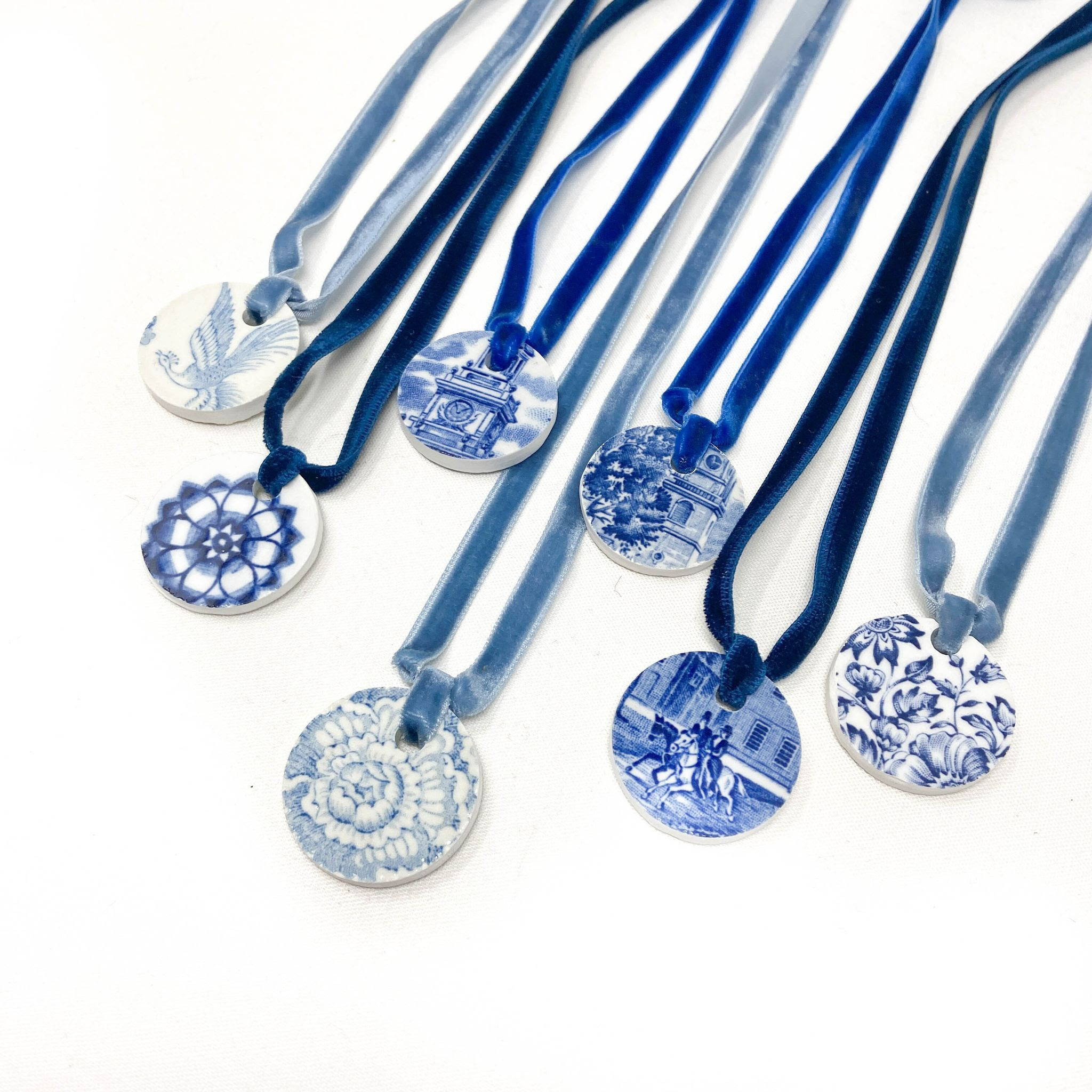 blue and white pendants made from upcycled transferware fine china by The Brooklyn Teacup - a few different styles lined up with velvet ribbon necklaces