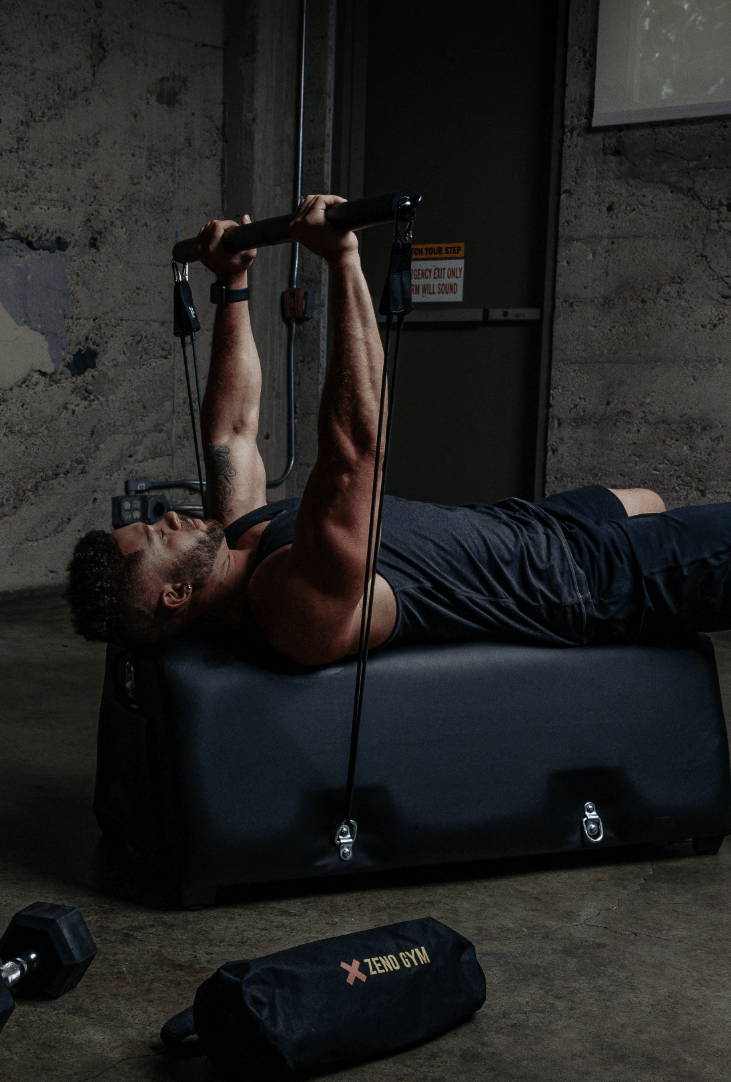 model demonstrates a bench press exercise with bench, resistance bands, and bar attachment.