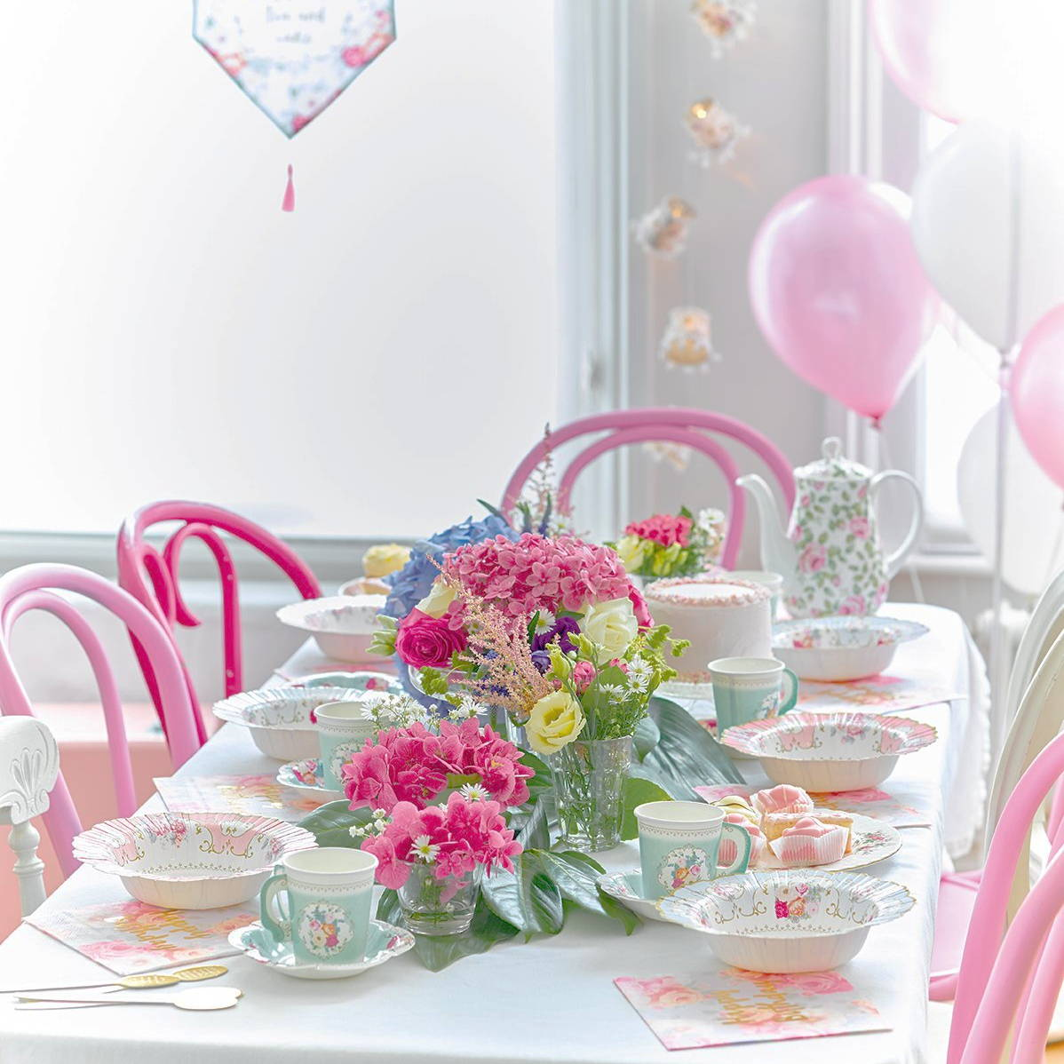 A photo of a baby shower party table laid out with the Truly Scrumptious baby shower range including floral party bowls, disposable party tea cups, and napkins