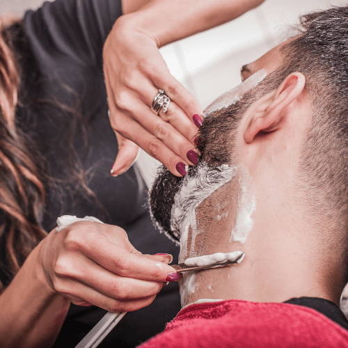 Female barber shaving neck beard