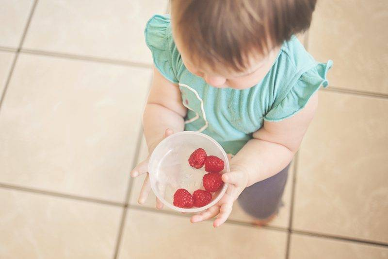 Baby Holding Fruit In A Bowl