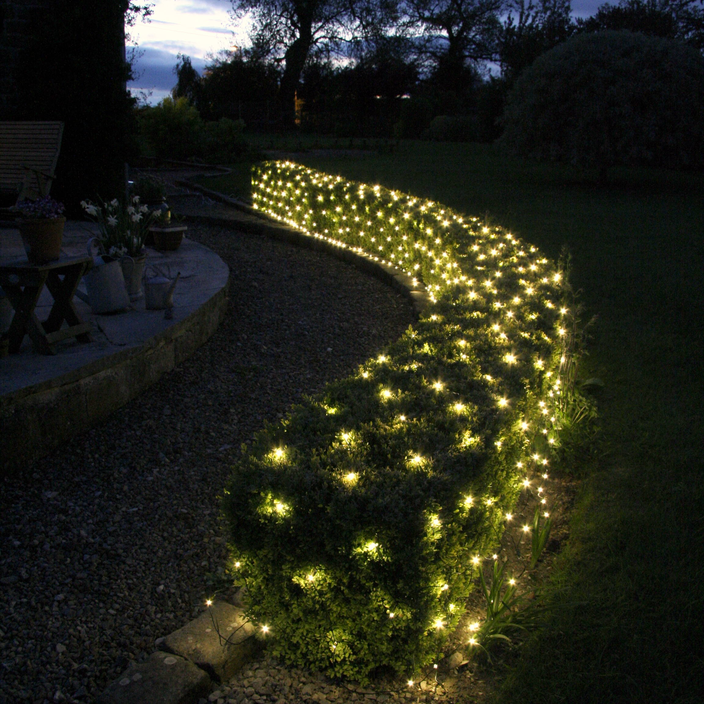 Warm white outdoor battery net lights in a Christmas garden