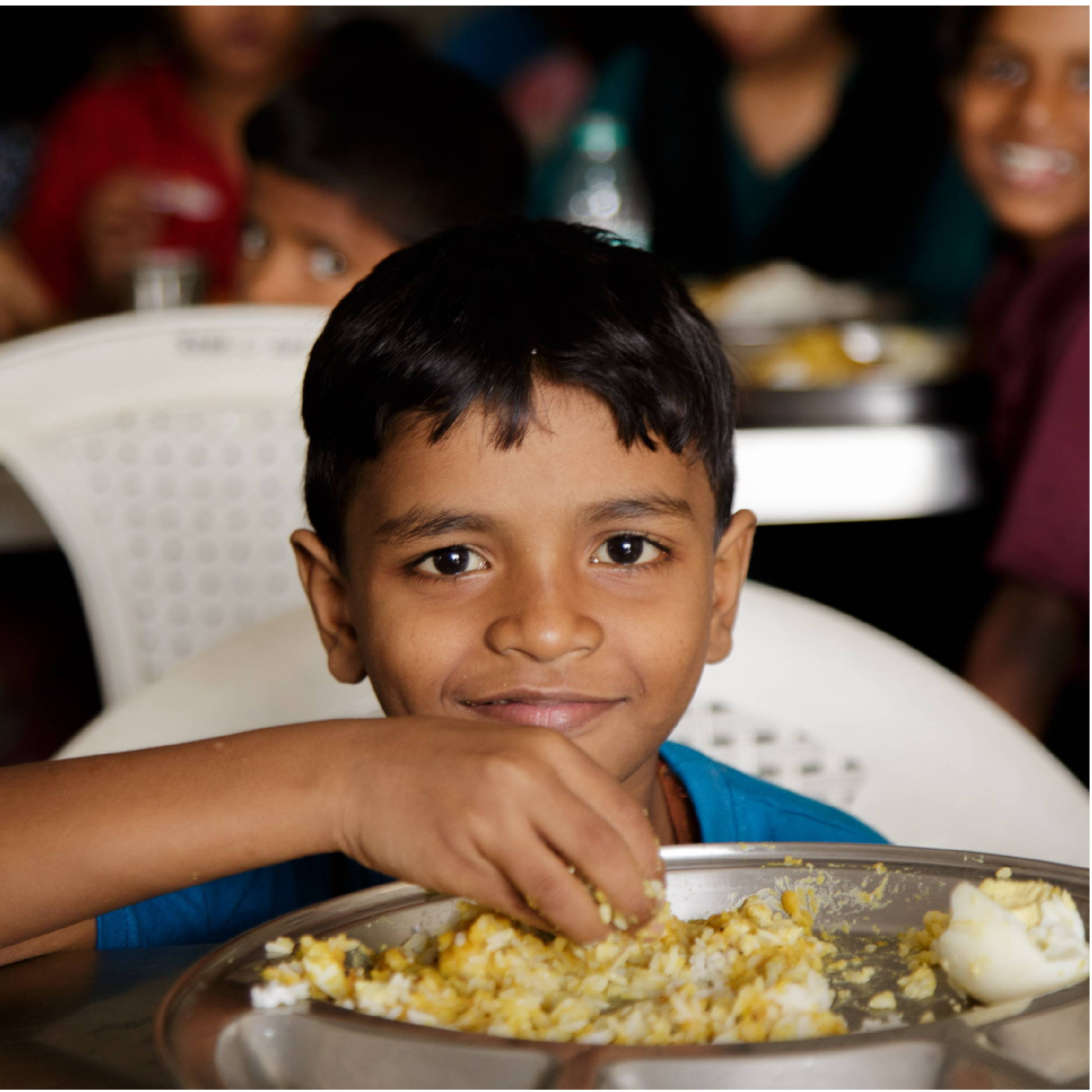 A young Indian boy sits at a table eating some rice and a hard boiled egg.