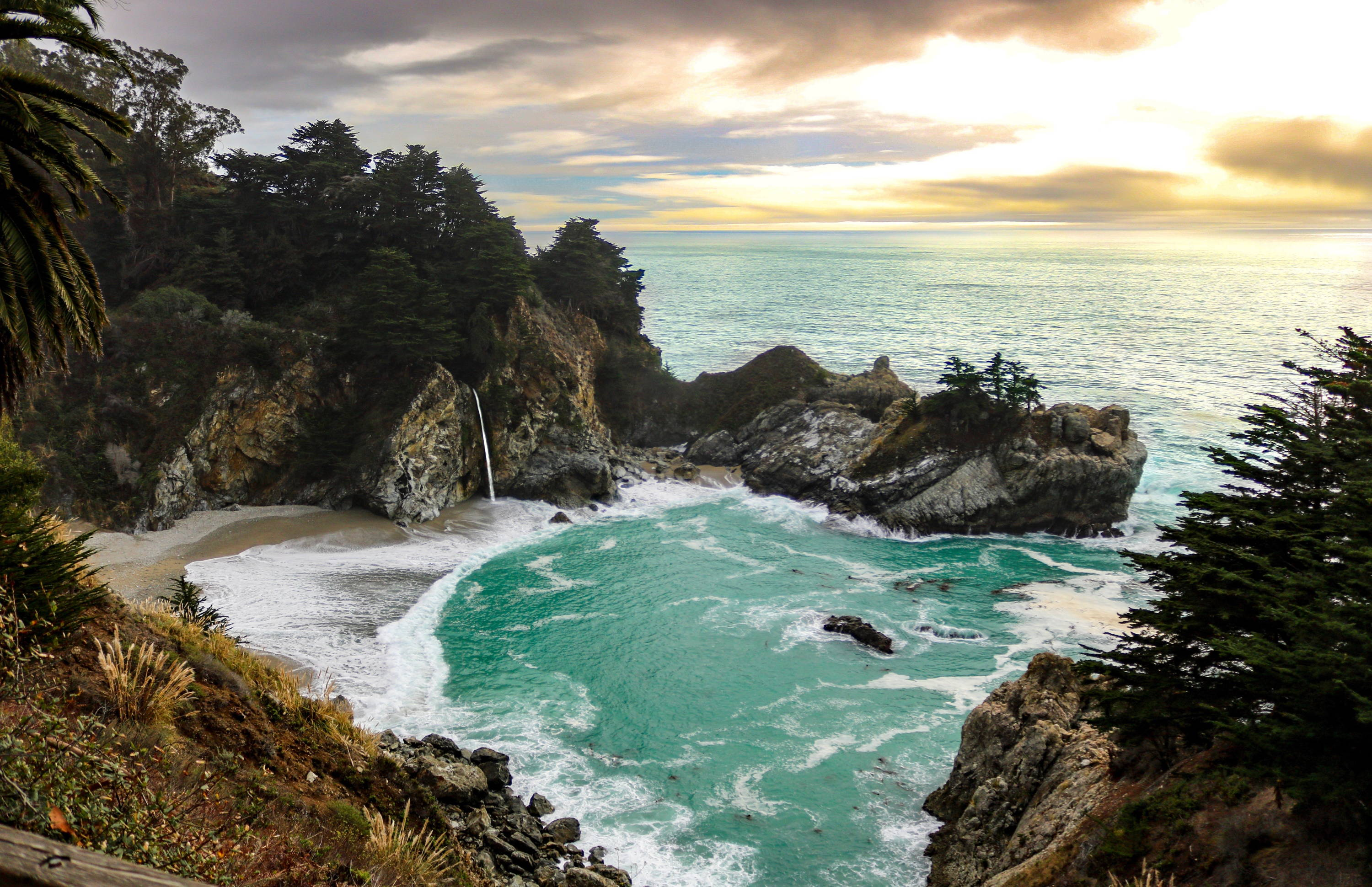 Big Sur Camping & Other Lodging Options. McWay Falls drops onto the beach with greenish-hued water nearby.
