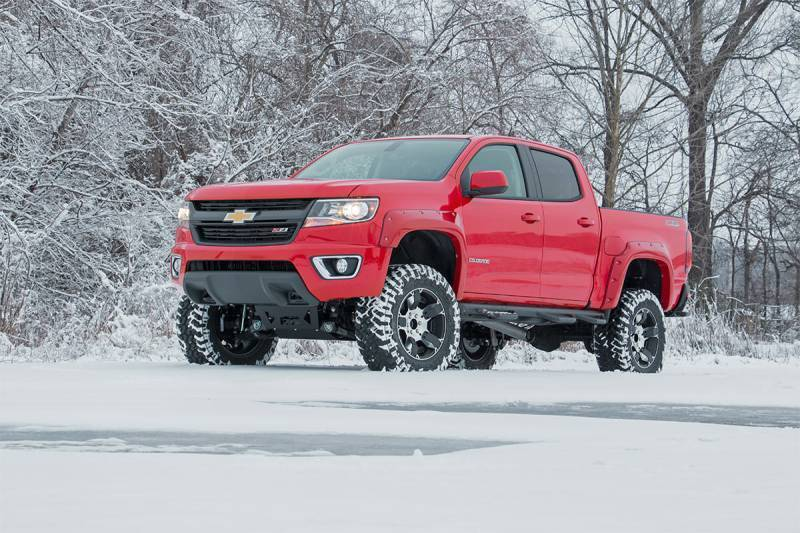 red lifted chevy truck in snow