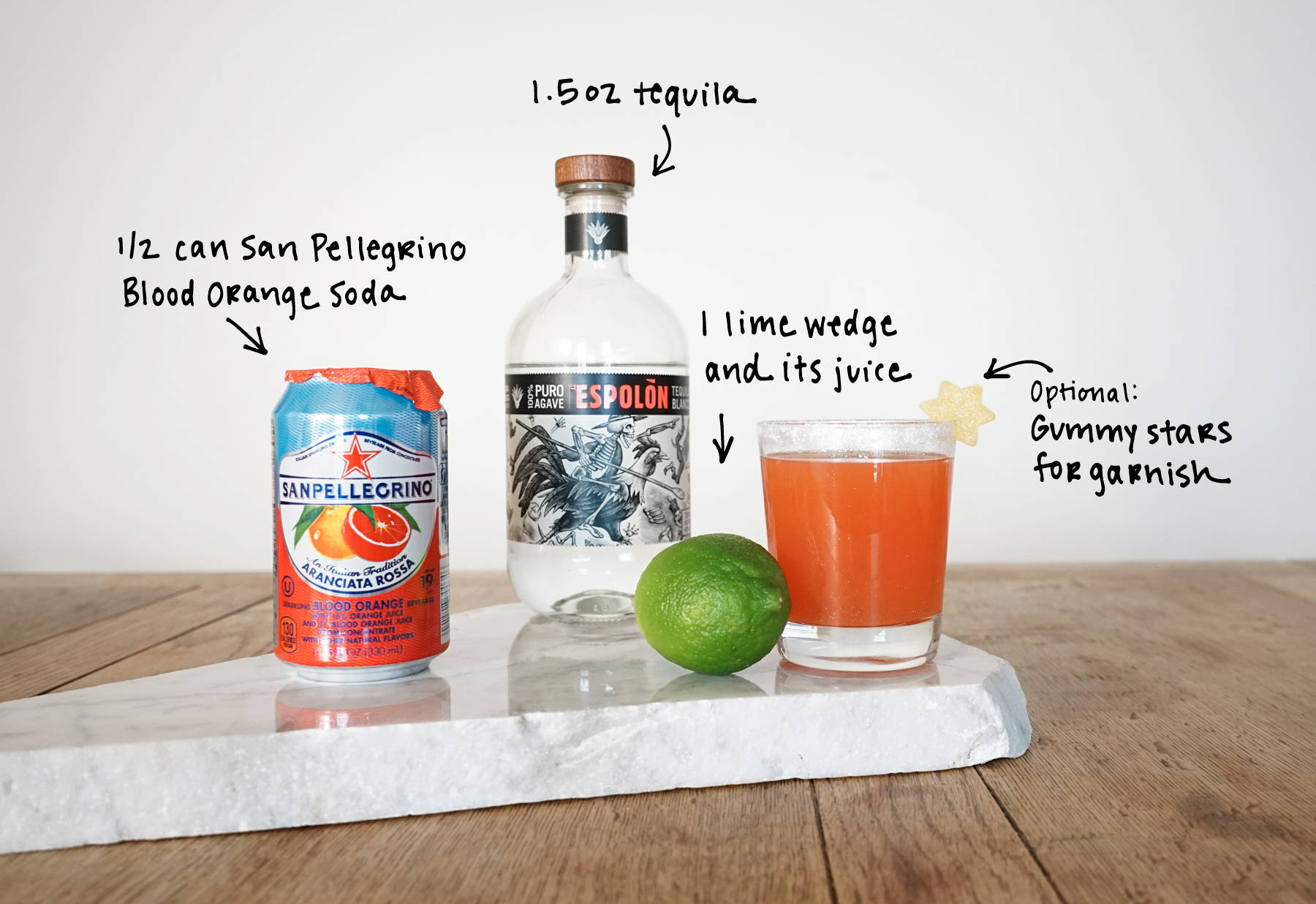 Unicorn Snot Spritz recipe with espolon tequila, san pellegrino blood orange soda, lime juice and dylan's candy bar gummies.