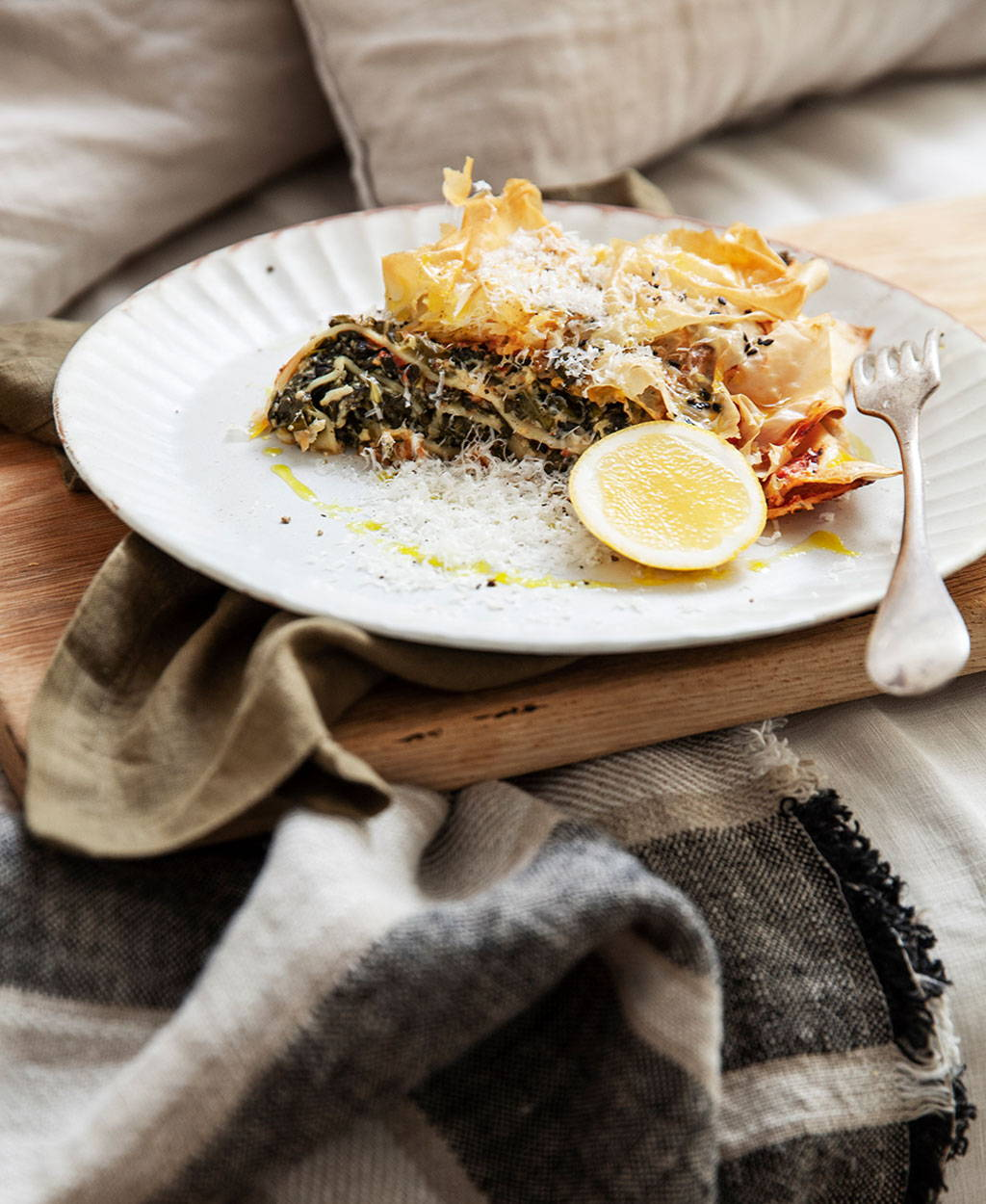 Spinach and Ricotta Lasagne with Cultiver table napkins in olive and a mira linen throw in enzo