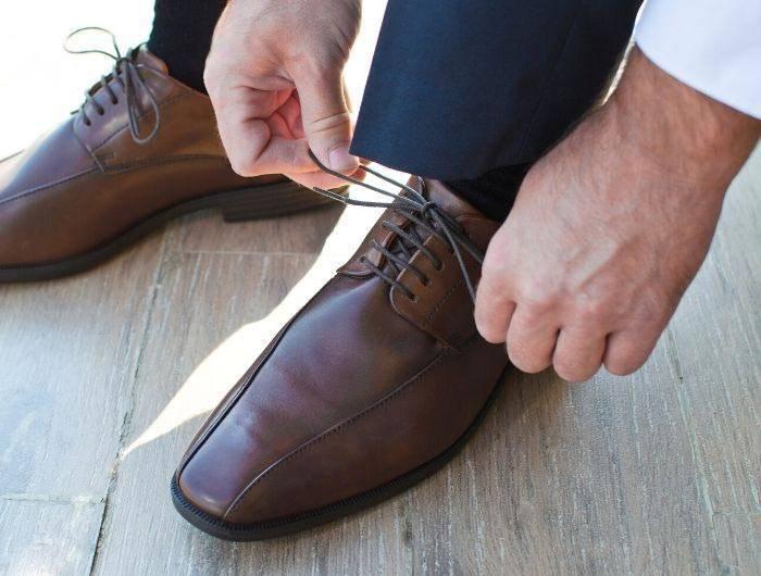 Man tying brown dress shoes