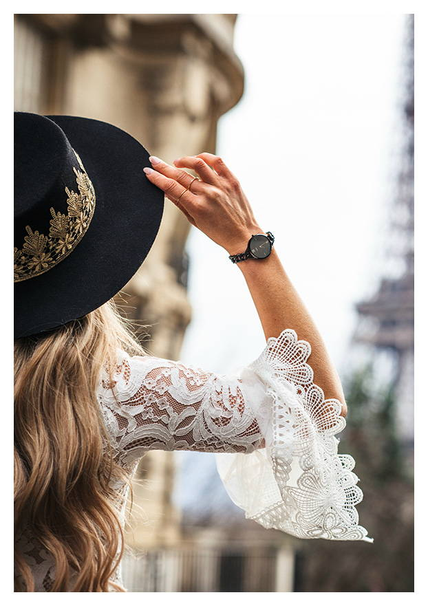 woman in a lace shirt wearing watch and hat