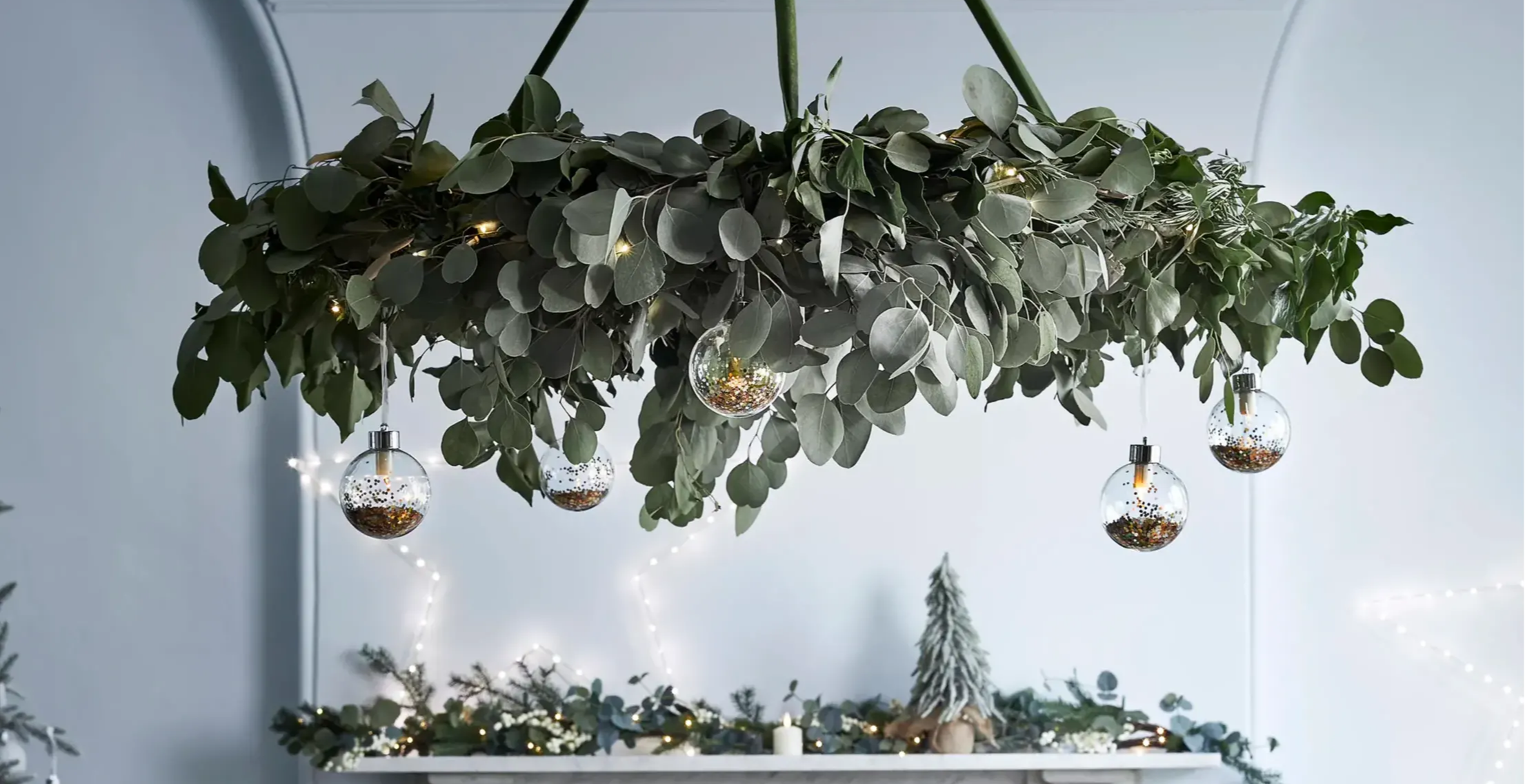 Close up image of foliage chandelier feature with mantel in the background featuring a festive garland, star light and mini tree