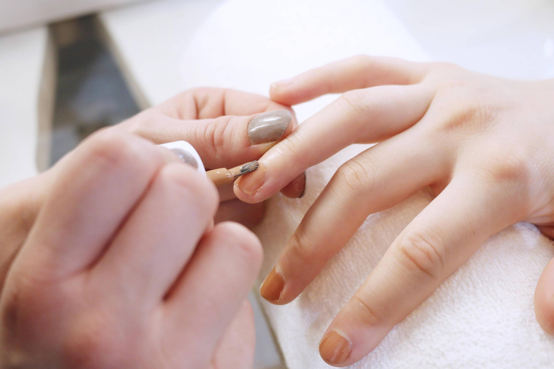 kosmetikerin lackiert einer kundin die nägel