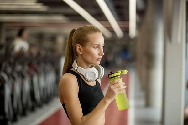 girl drinking bcaa powder at gym