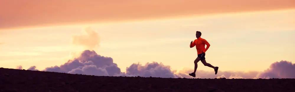 Man jogging against the sunrise