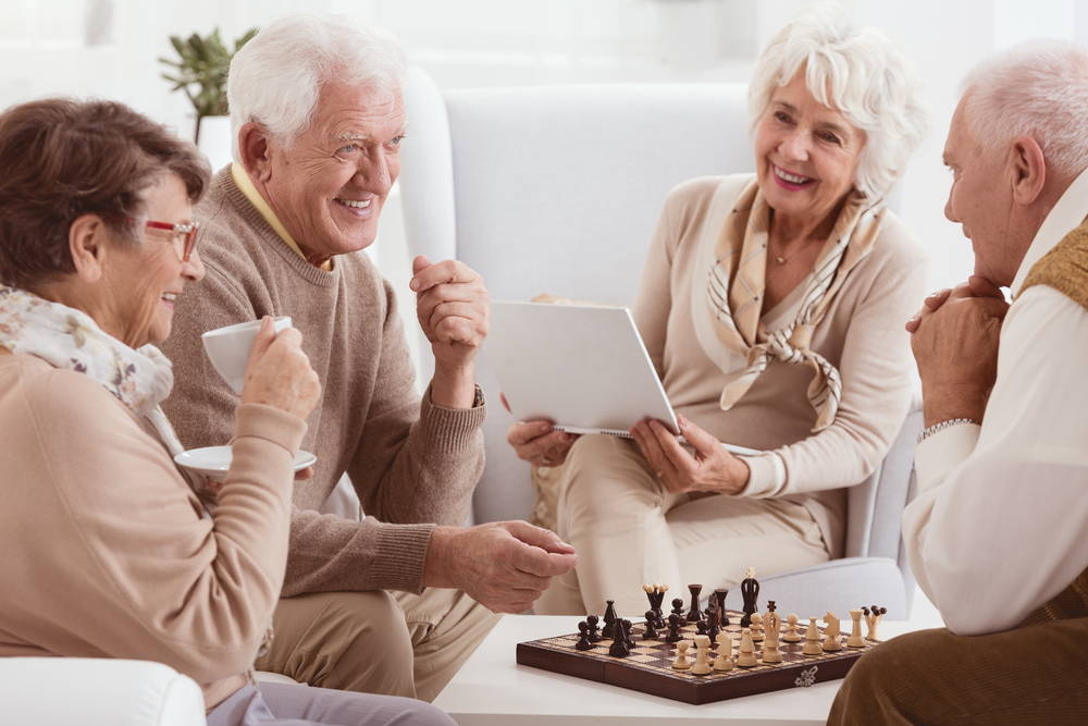 A group of elderly people interact in pleasant conversation.