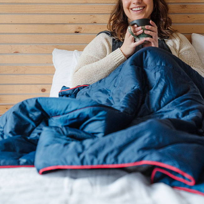 Woman curled up on her bed sipping coffee under a Rumpl blanket