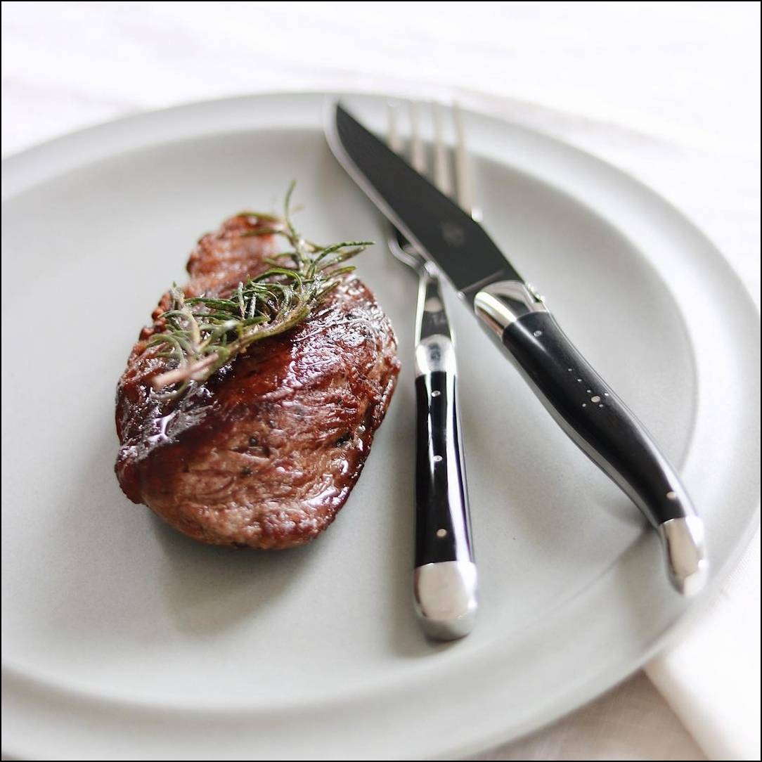 Laguiole steak knife and fork on a white plate next to a piece of red meat.