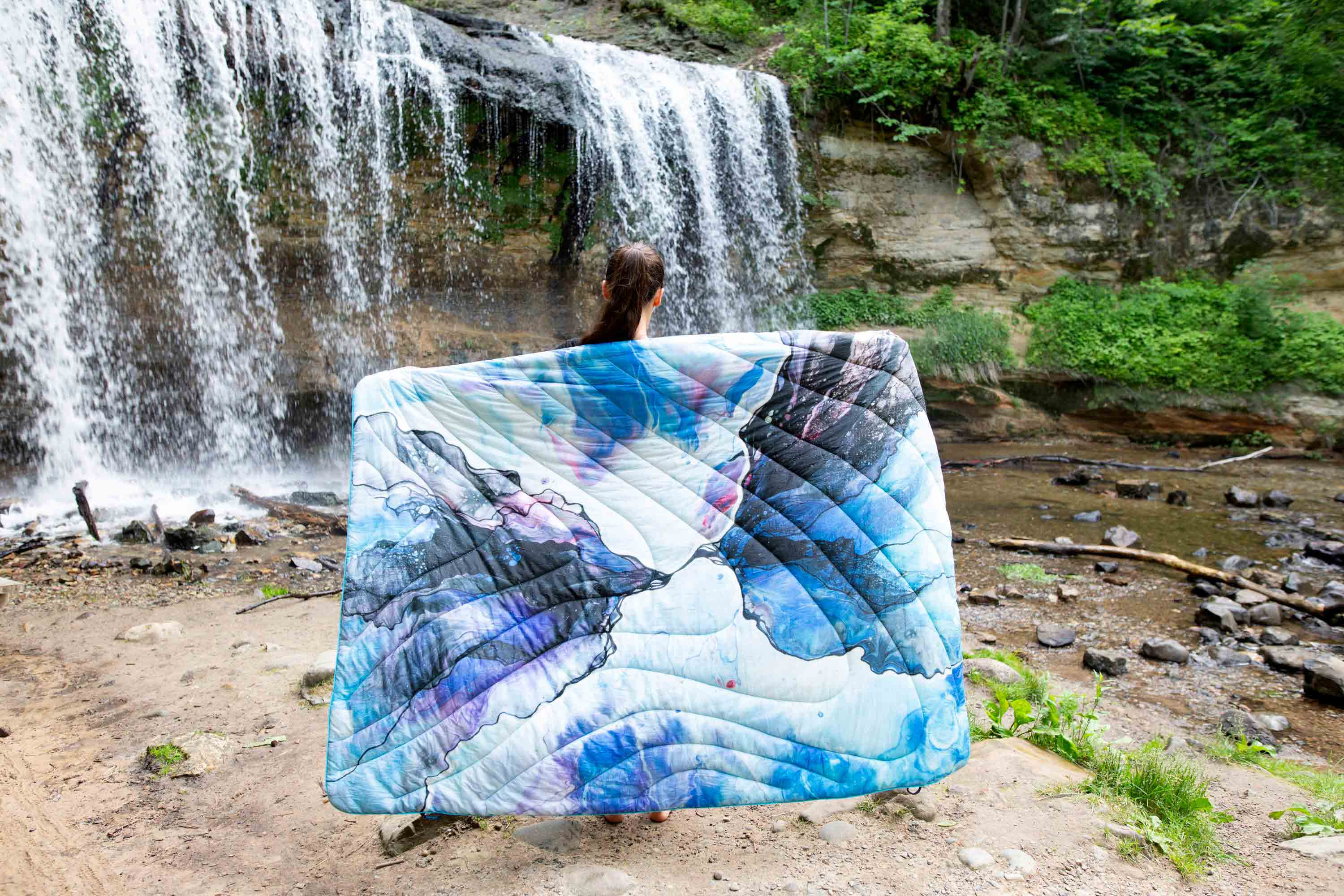 Women standing in front of a waterfall with Rumpl blanket