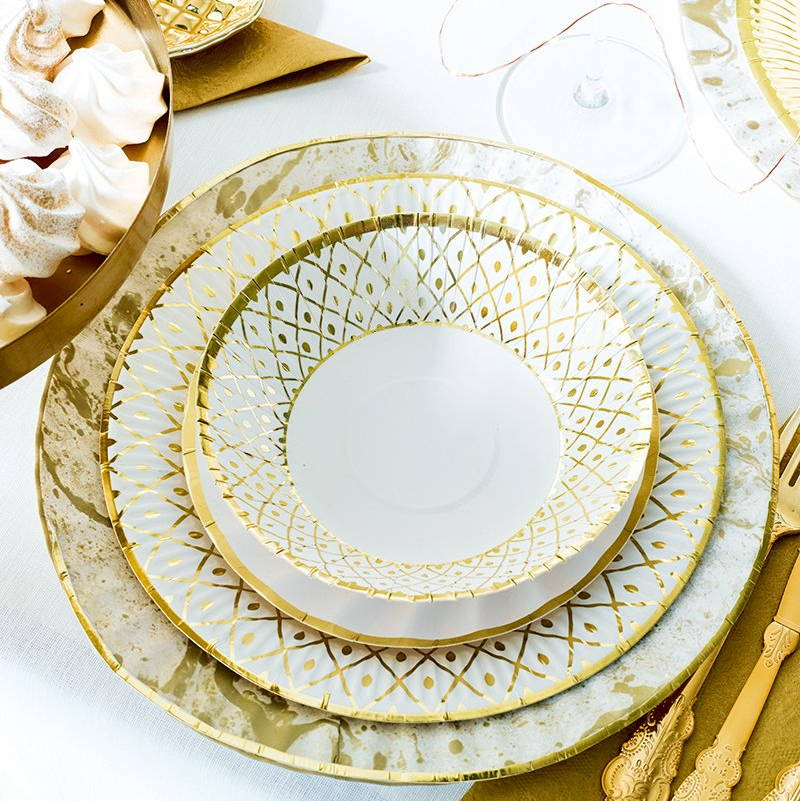 A photo of a party table setting, laid out with tableware with a bottom main plate, then slightly smaller plate and a third smallest on top plus bowls, all in white with gold edging and decoration patterns