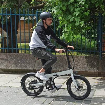 A young man riding his folding electric bike riding through the streets.