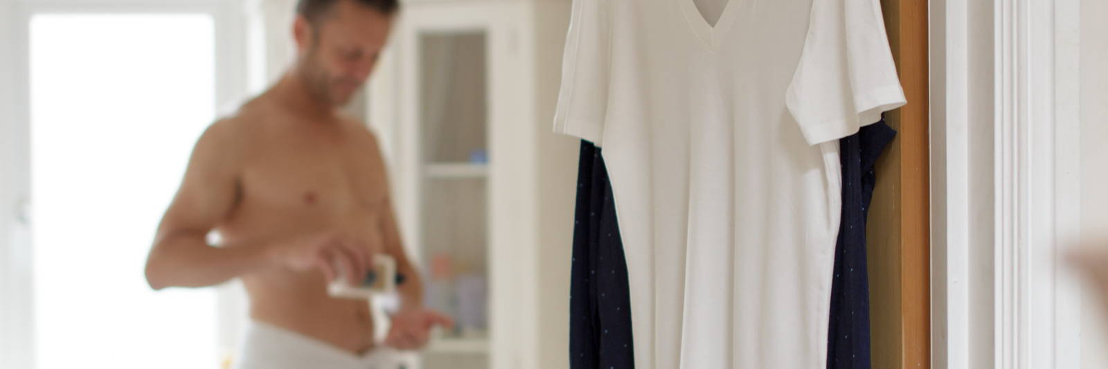 A picture of a white undershirt handing on a bathroom door with man in the background applying aftershave