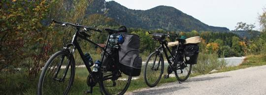 Two bicycles packed with camping gear parked on the side of a mountain road
