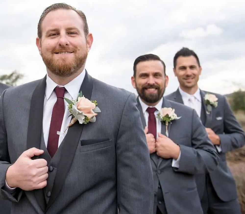 Groomsmen wearing burgundy ties and gray suits