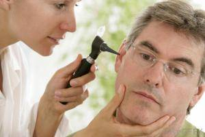 Female doctor using otoscope to look into ear of man with glasses