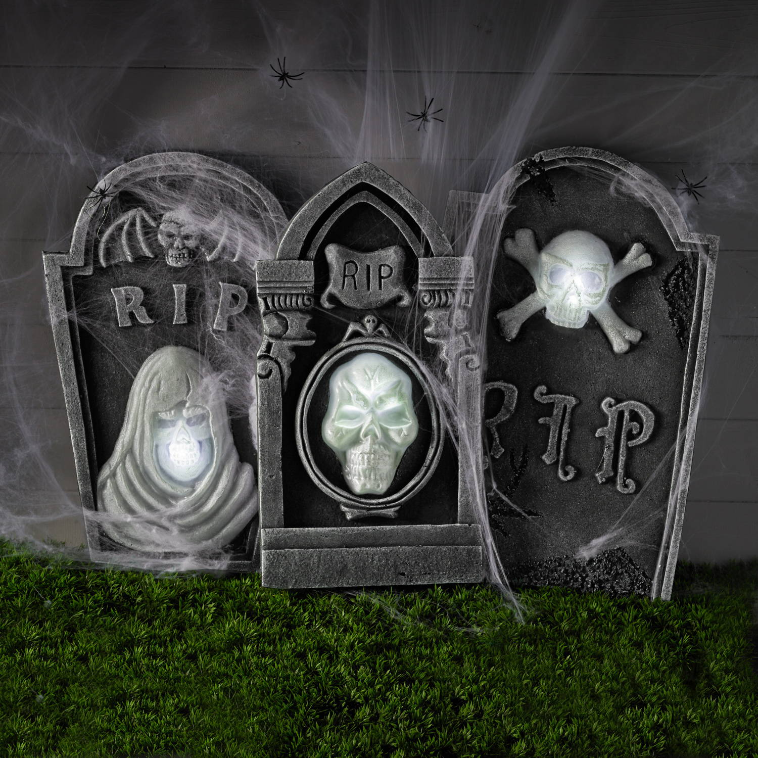 3 Illuminated Deathly Gravestone Props covered in cobwebs and spiders for a Halloween display