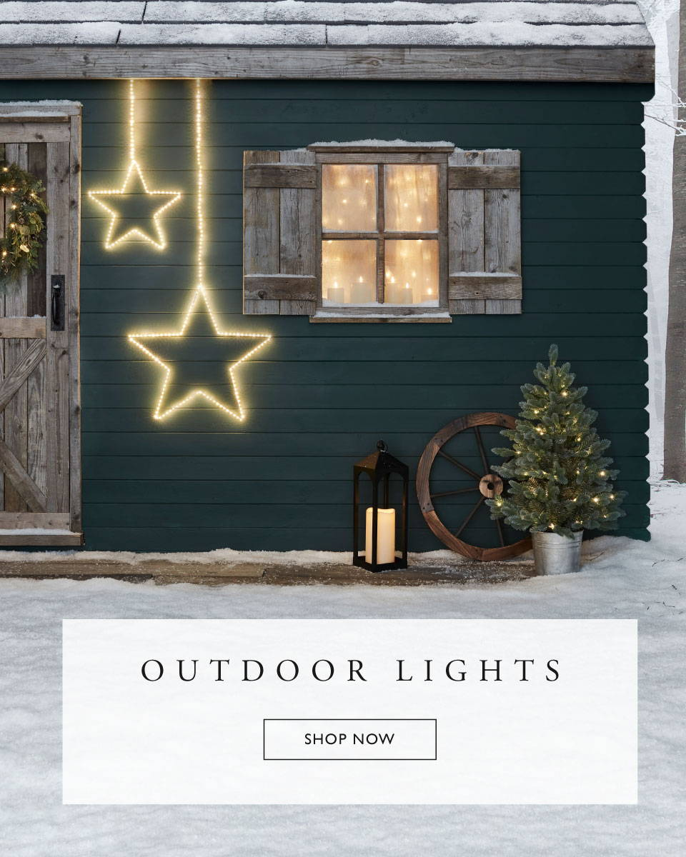 A green Christmas cabin with star lights and outdoor Christmas decorations