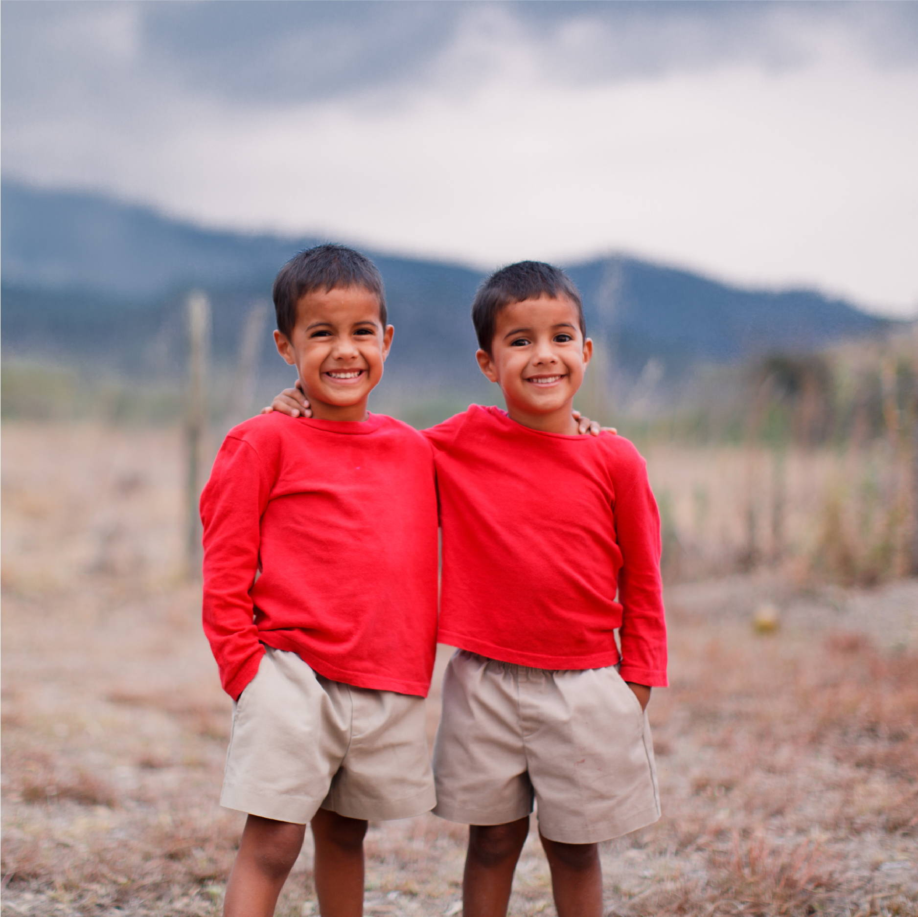 two young Honduran boys wear khaki shorts and red shirts as they stand and smile in front of a mountain range in Honduras.