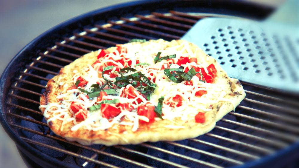 pizza on a grill with tomatoes and basil and cheese